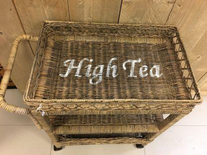 Rieten Thee Kar Met de tekst HIGH TEA! Echt een sfeer maker in de keuken! Ook erg leuk in een landelijke woonkamer! te gebruiken als bijzet tafeltje of kastje. Er zitten handige zwenk wielen aan de thee kar maar die kunnen er ook af!
